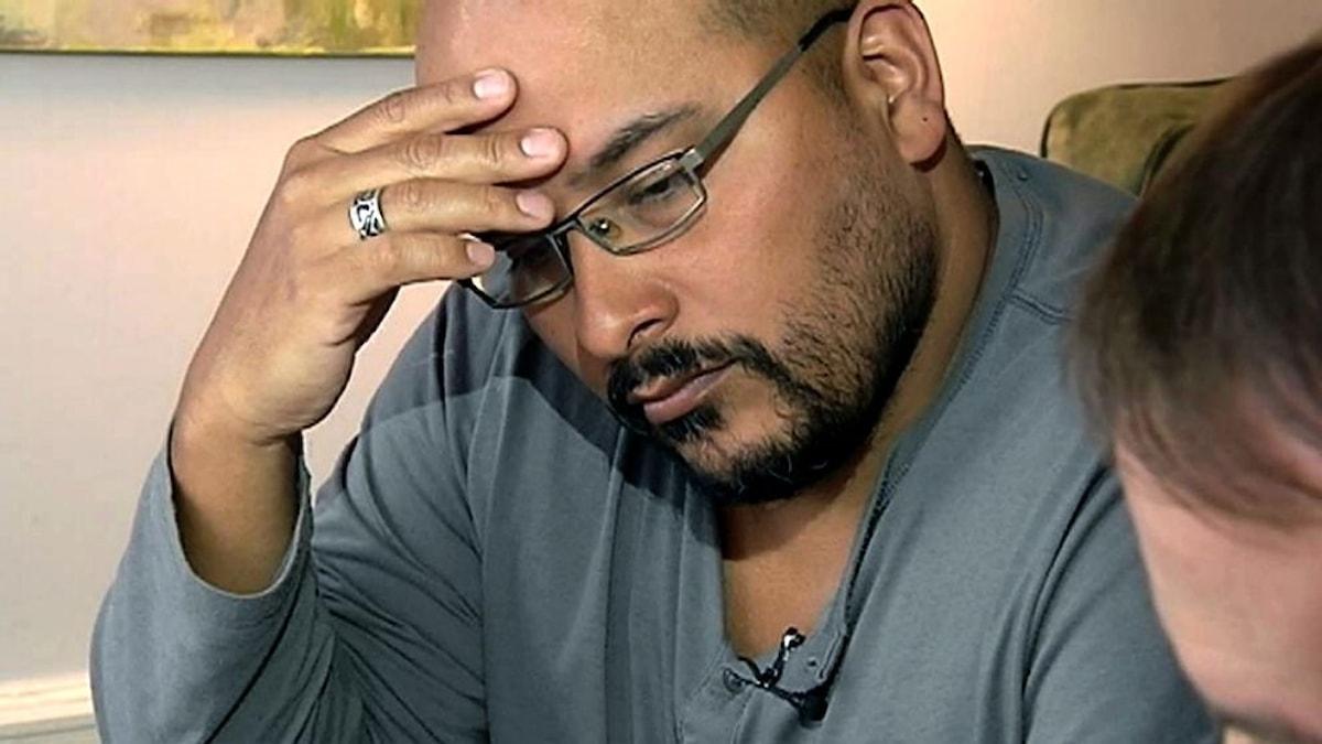 Bilden visar en bekymrad man som tittar ner med handen på pannan. Han har glasögon och skägg.