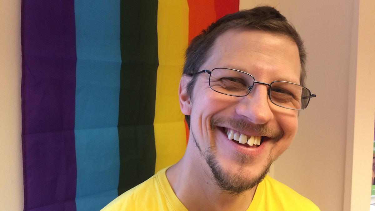 Peter har skägg och glasögon. Bakom honom hänger en hbtq-flagga i färgerna rött, orange, gult, grönt, blått och lila.