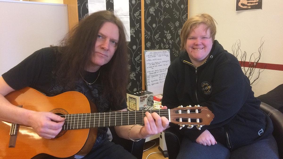 En man med gitarr och en tjej i kort blont hår.