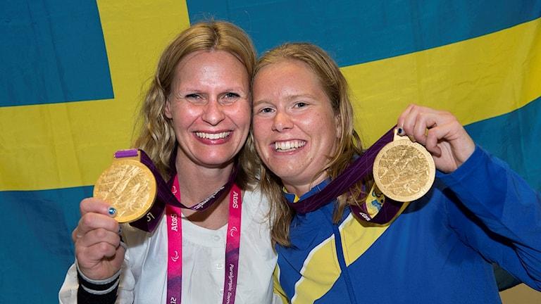 De håller upp sina medaljer. Bakom dem finns en svensk flagga.