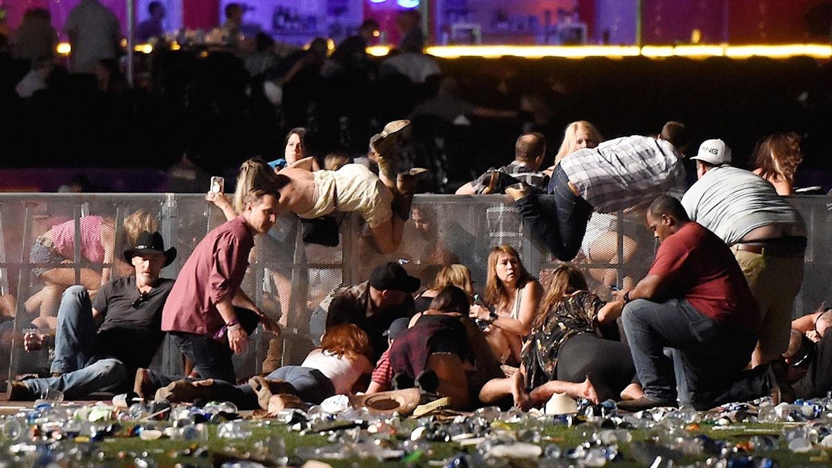 Människor kryper ihop vid ett staket för att söka skydd.