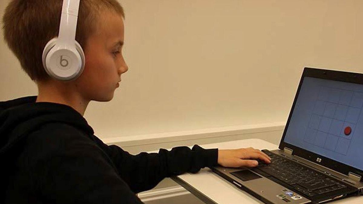 På fotot sitter en ung pojke framför en dator och han har hörlurar på sig.