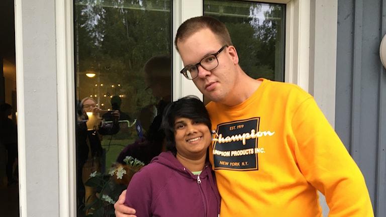En man och en kvinna står utanför ett hus och ser glada ut och kramar varandra.