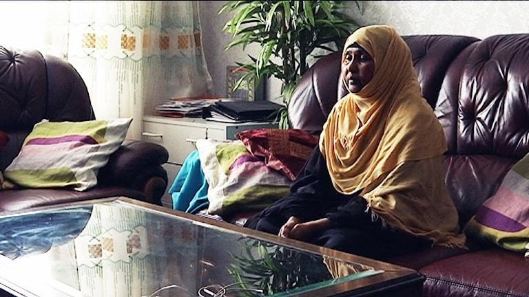 En somalisk kvinna i engul huvudduk sitter i en soffa.