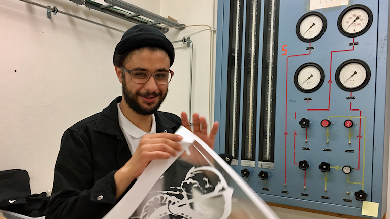 På fotot håller Hally upp den mall som används i tryckeriet. Han är klädd i en svart kofta och har en svart mössa.