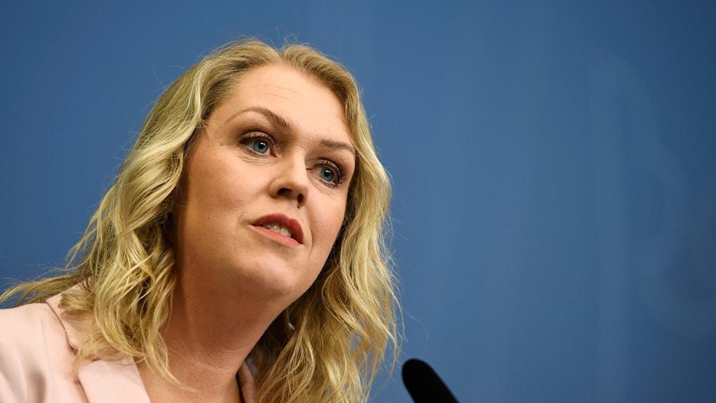 På fotot ser man Lena Hallengren. Hon har en rosa kavaj och lockligt blont hår.