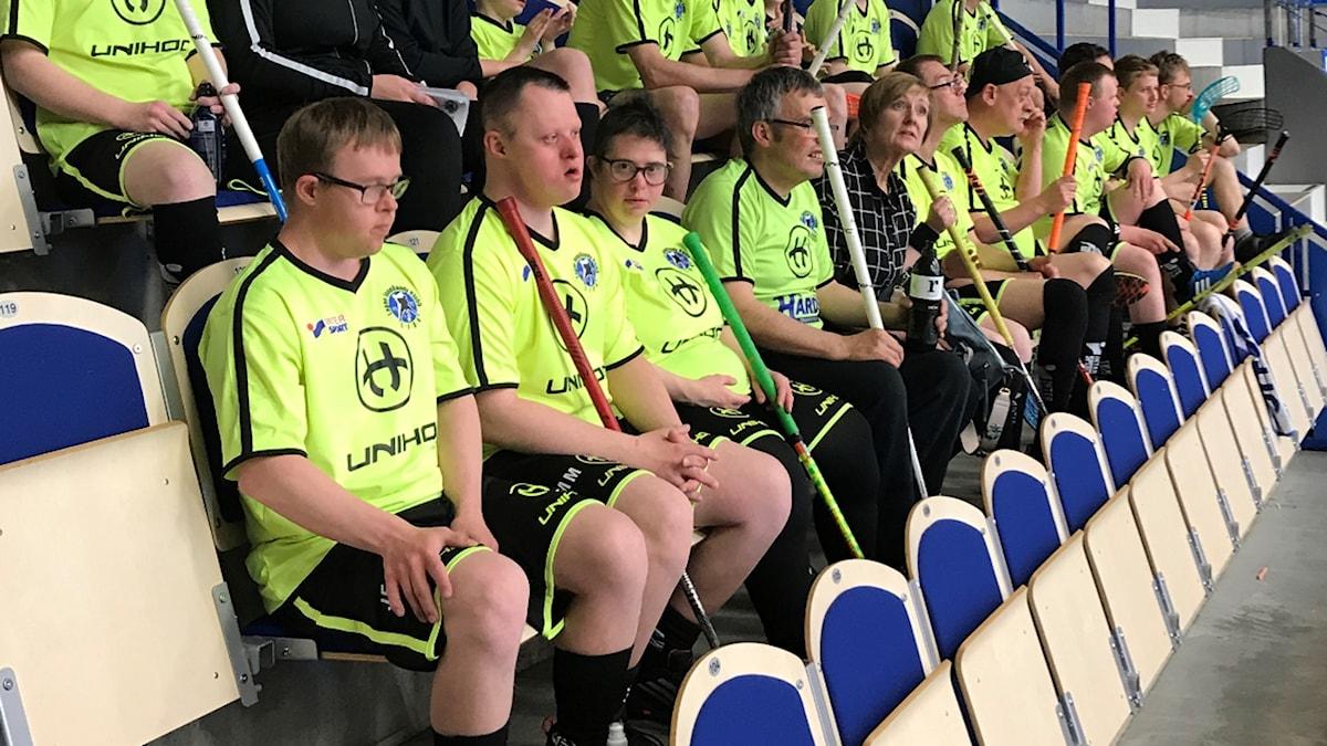 Innebandyspelare i gula tröjor och svarta shorts sitter på läktaren