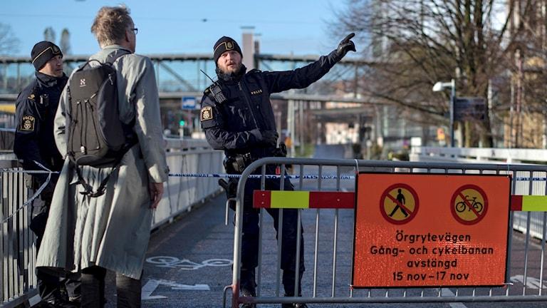 På fotot syns en väg som är spärrad med betongklumpar och staket. Två poliser pratar med en person som kommer gående.
