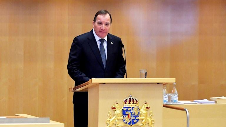 På fotot står Stefan Löfven i talarstolen. På talarstolen finns en blå vapensköld som hålls upp av gyllene lejon.