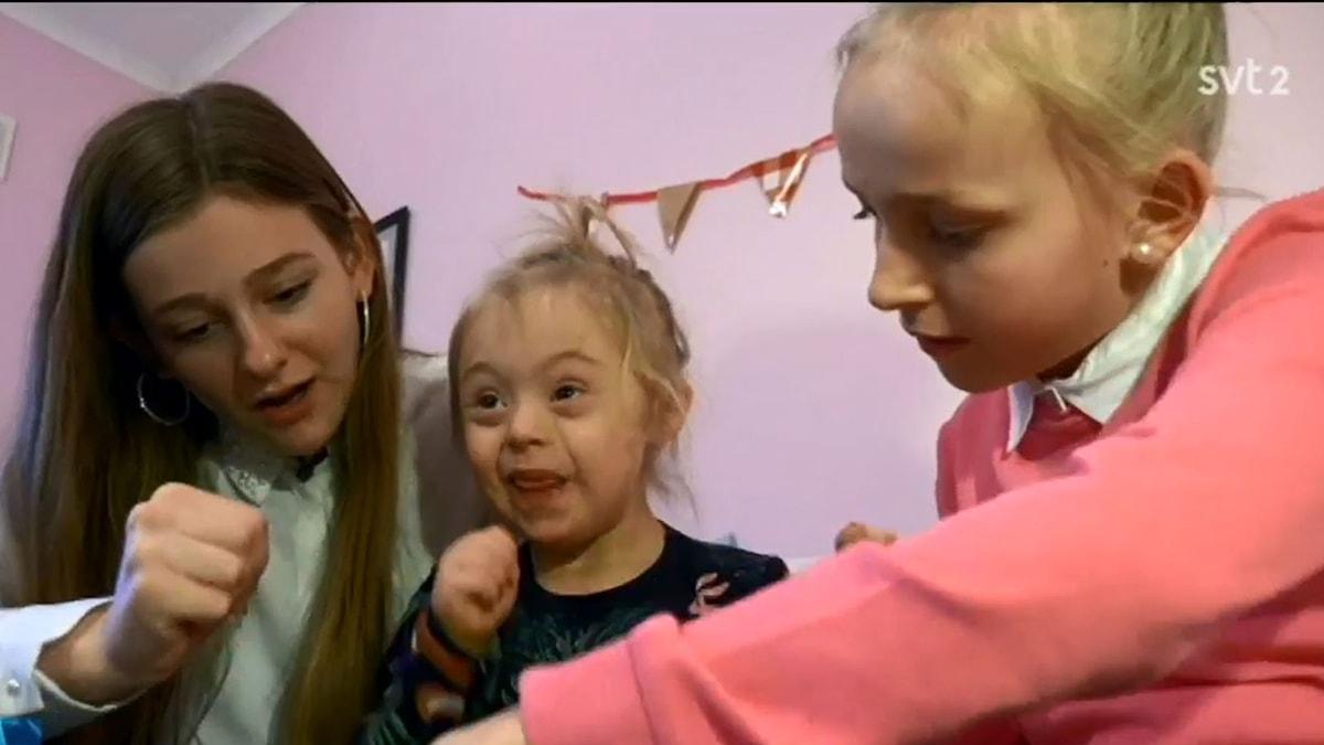 Fotot visar tre systrar, där en har Downs syndrom
