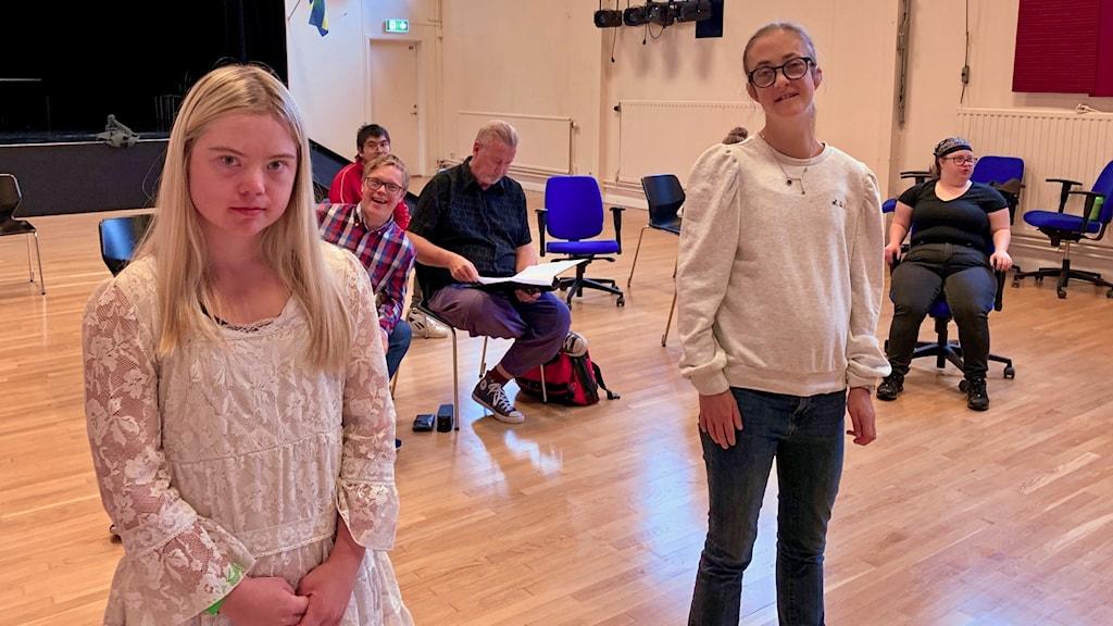 Linnéa Dahl och Agnes Stahlman står i en aula framför några klasskamrater.