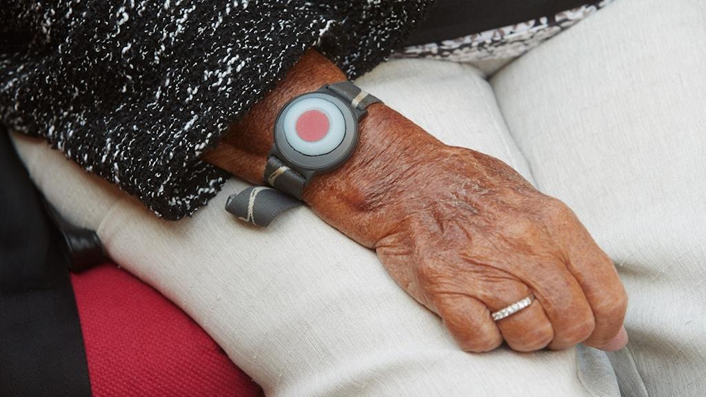 En äldre person med ett trygghetslarm på sin handled. Larmet har en knapp som man kan trycka på när man behöver hjälp.