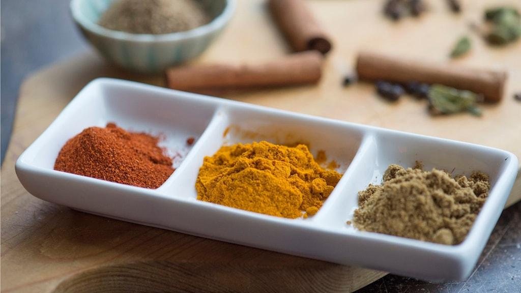 På ett bord finns flera olika kryddor. Gurkmeja har en gulorange färg.