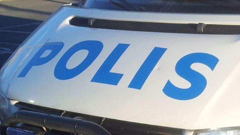 Huven på en vit bil där det står polis i blått