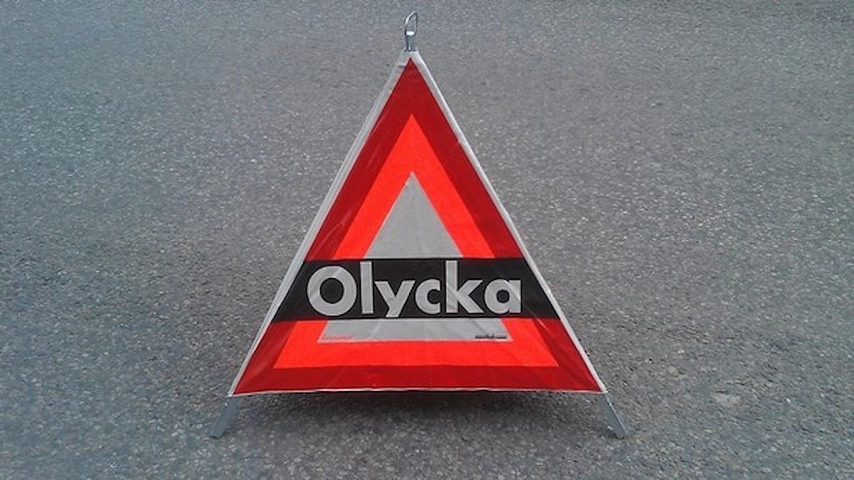 """Skylten är en röd triangel som står på vägen. På skylten står det """"olycka""""."""