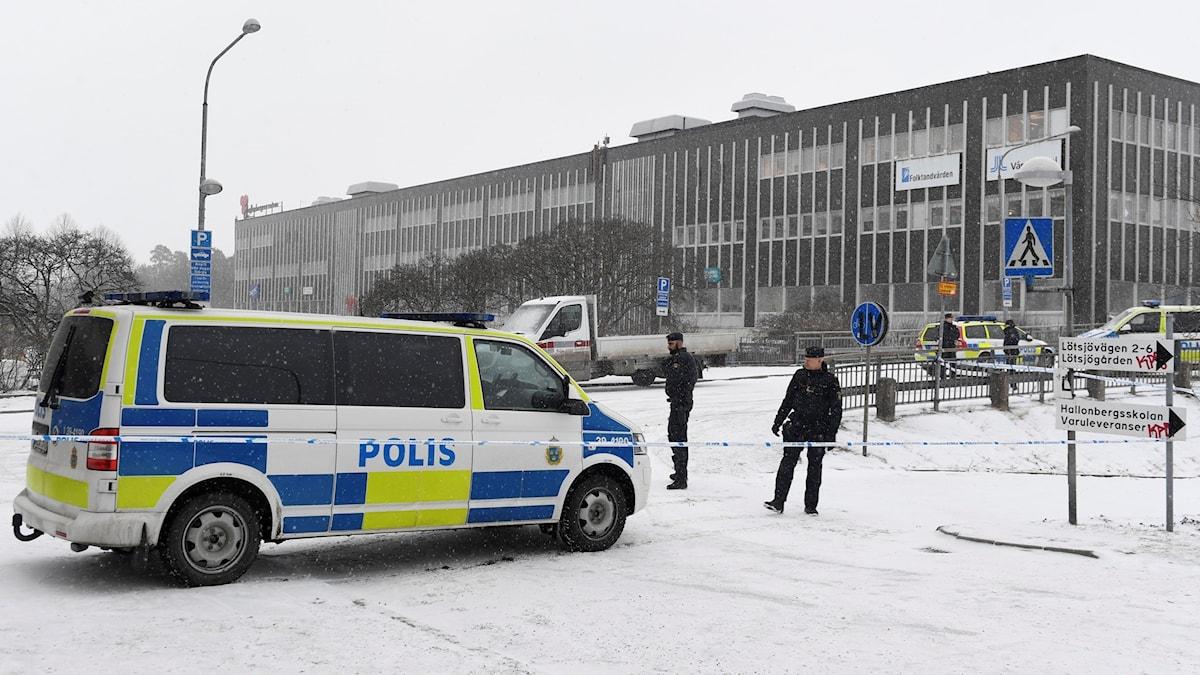 Det är snöigt ute. På bilden syns några poliser och en polisbil. I bakgrunden finns ett stort fyrkantigt hus.