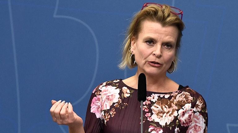 På fotot pratar Åsa Regnér i en mikrofon. Hon har satt upp sina glasögon i håret.