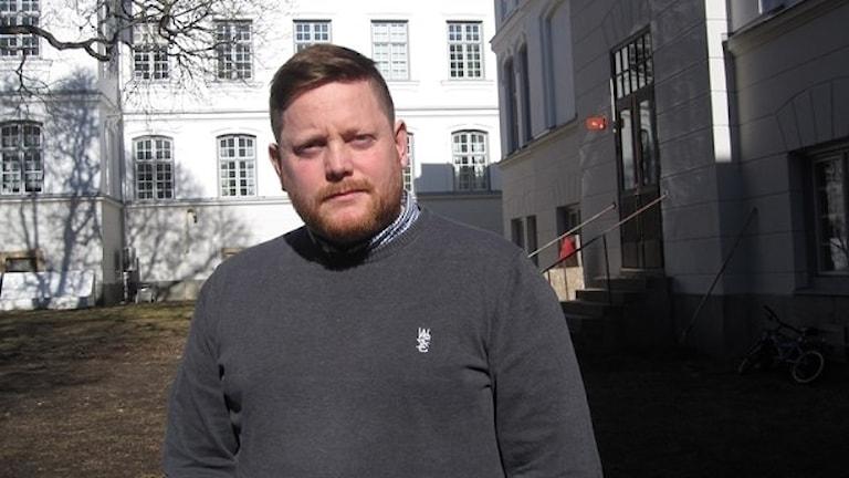 Anders är klädd i en grå tröja med en skjorta under. Han har skägg. Skolhuset är vitt och byggt i en gammaldags och pampig stil.