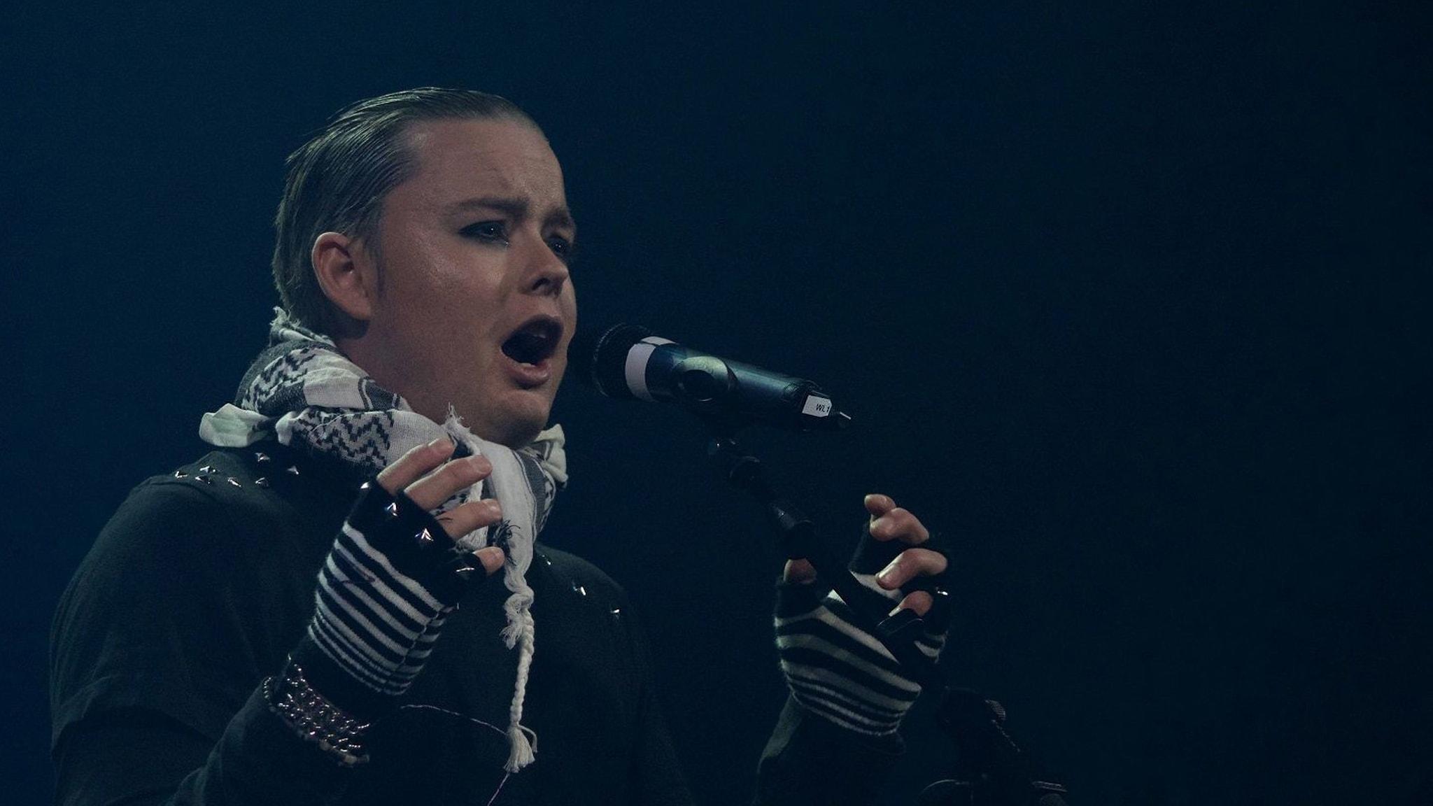 På fotot sjunger Martin Hagen. Han är svartsminkad runt ögonen och han har på sig svarta kläder med nitar.