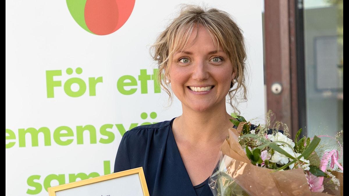 Katrin Andersson med blommor och diplom.
