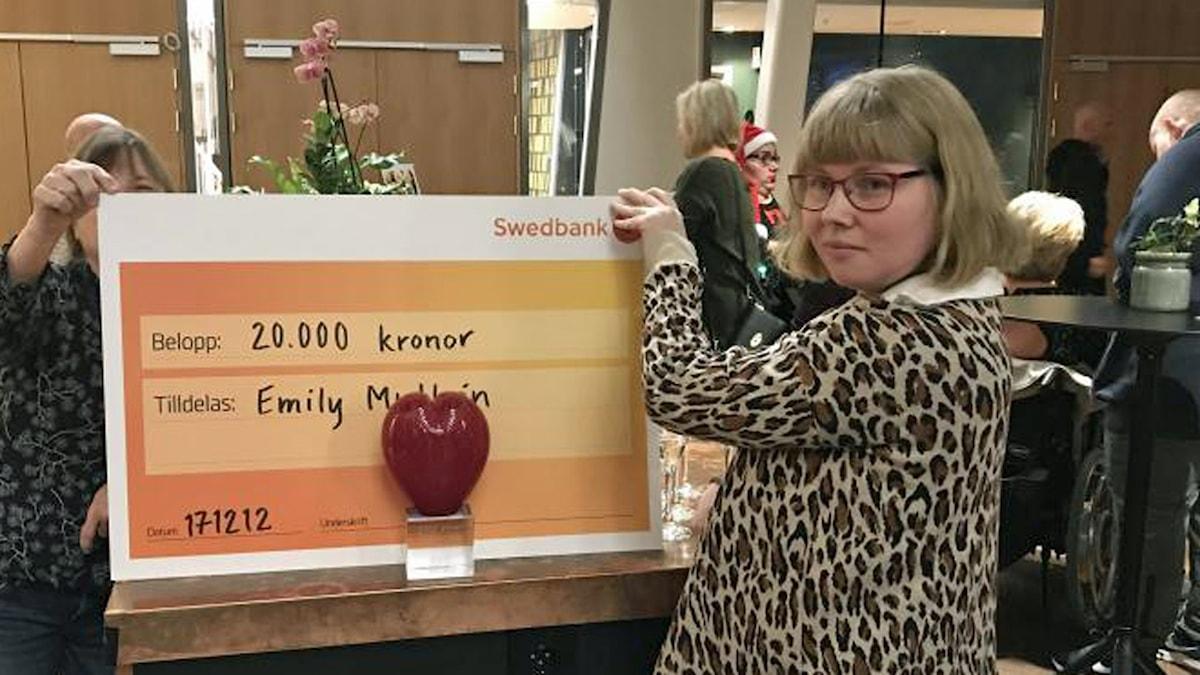 På fotot håller Emily upp en check. Checken är ett jättestort kartongpapper där det står hur mycket pengar hon får.
