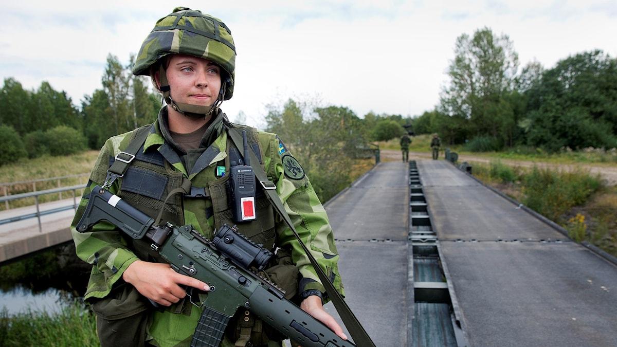 En kvinnlig soldater vaktar en bro. Hon är klädd i kamoflagekläder och har ett vapen.