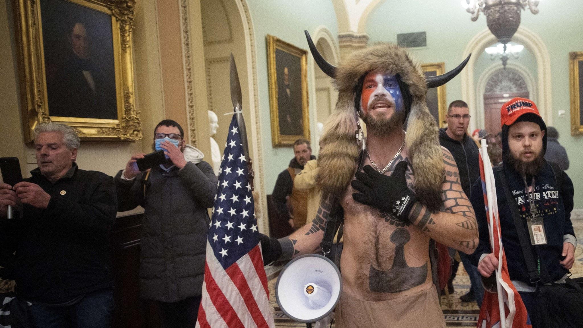 På fotot syns bland andra en man som är naken på överkroppen. Han har en pälsmössa med horn på huvudet.
