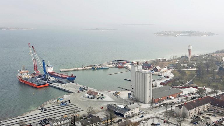 Det är en grå och disig dag och ett stort fartyg ligger i hamnen.