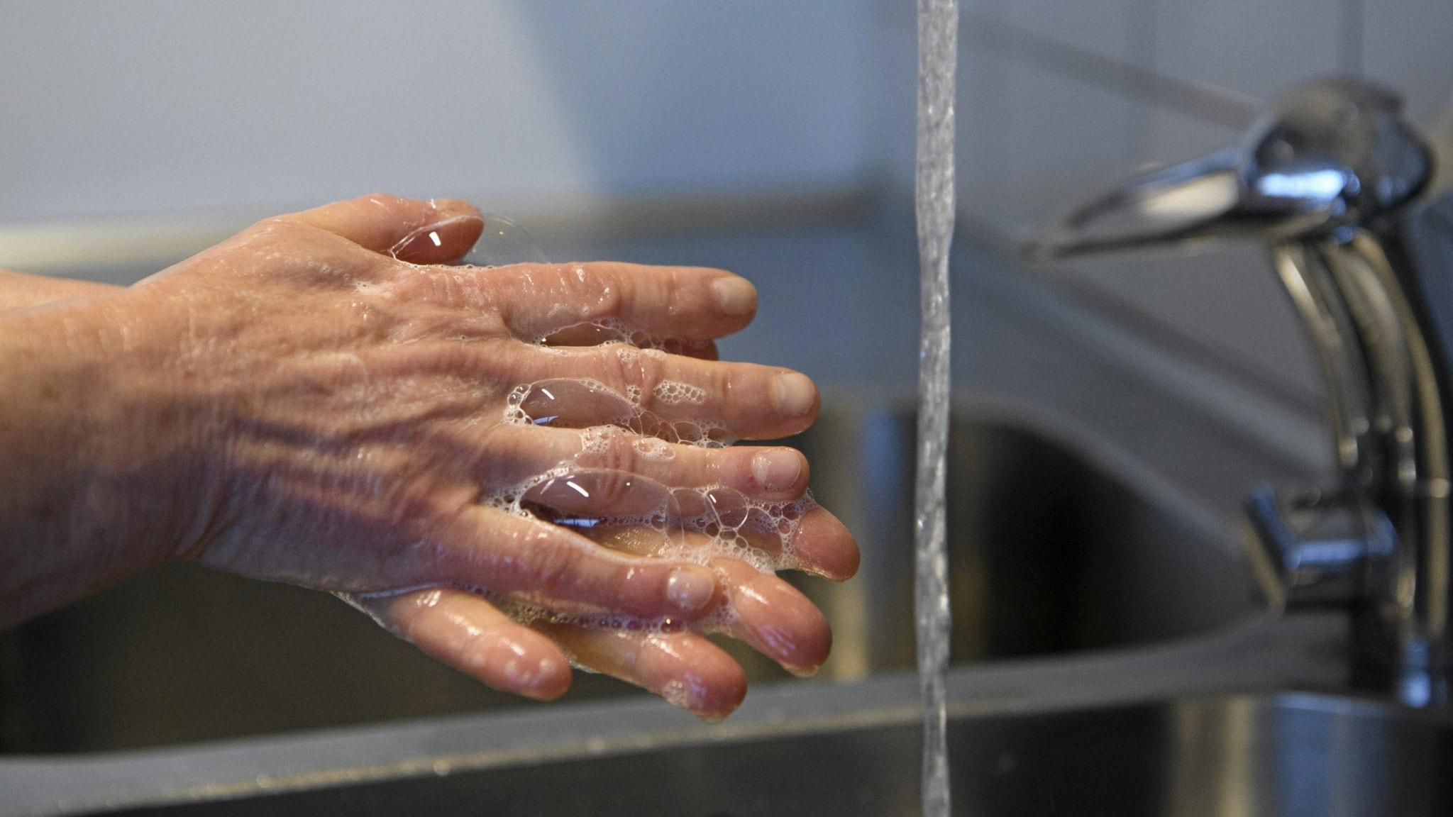 en person som tvättar händerna