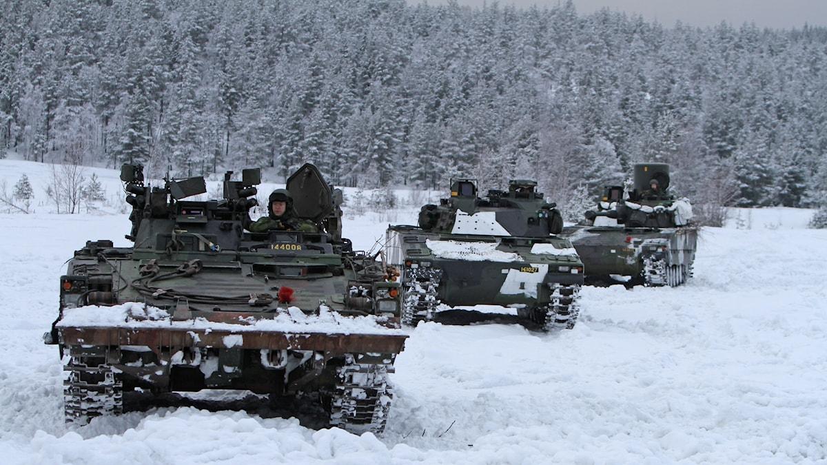 Tre bandvagnar kör genom snön. Istället för däck har de band som snurrar runt.