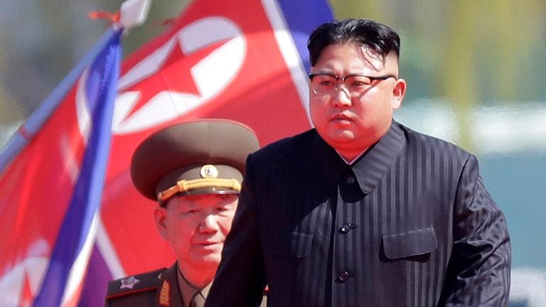 Kim har en frisyr med renrakat på sidan av hududet och sedan lite hår uppepå. Han är klädd i kostym. Bredvid honom finns en militär i uniform.