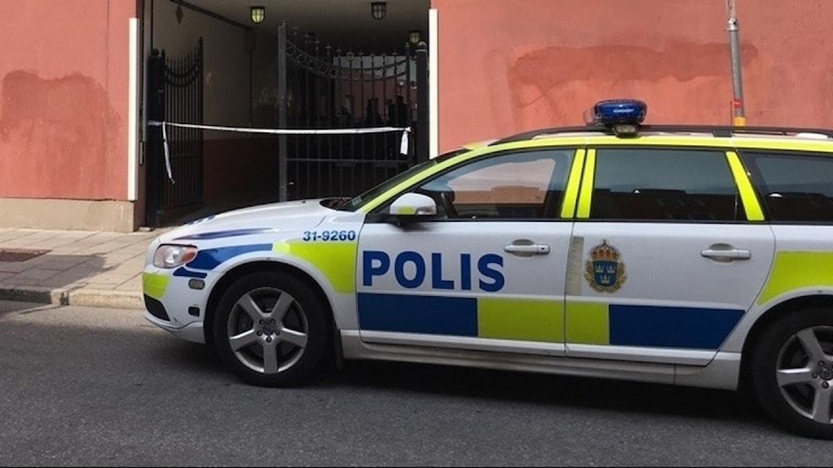 På fotot ser man att ett plastband spärrar av en portuppgång. Utanför står en polisbil.
