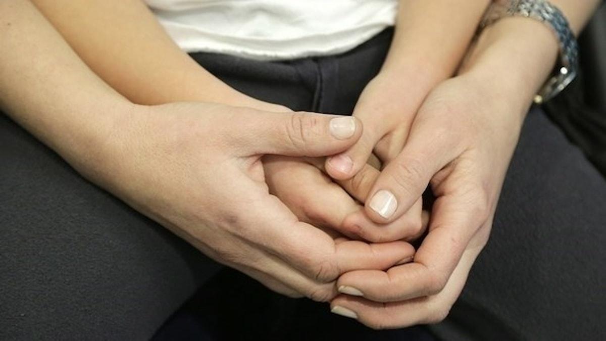 En yngre person sitter i knäet på en äldre och de håller händer.