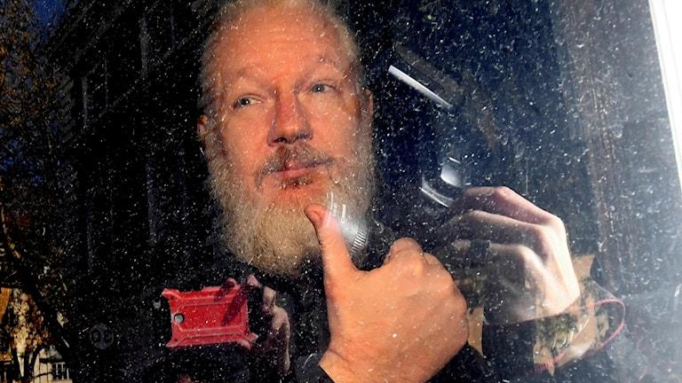 På fotot syns Julian assange bakom en bilruta. Han har vitt hår och vitt skägg. Han gör tummen upp.