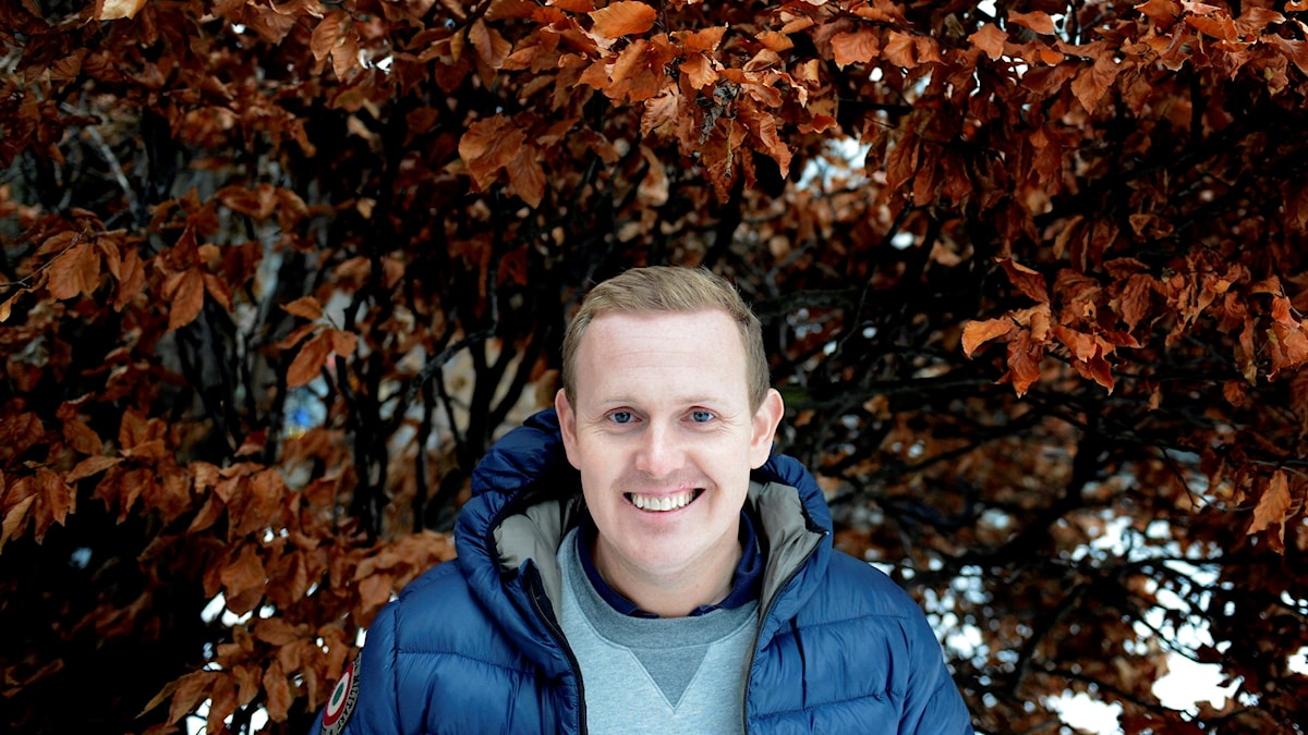 På fotot syns komikern Måns i blå täckjacka i en park med höstträd.