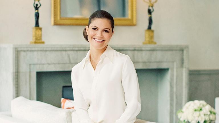 Kronprinsessan Victoria har en vit skjorta och sitter på en soffa framför en eldstad.