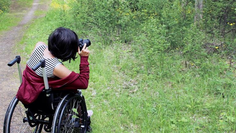 På fotot ser man en ung tjej i rullstol som fotograferar.