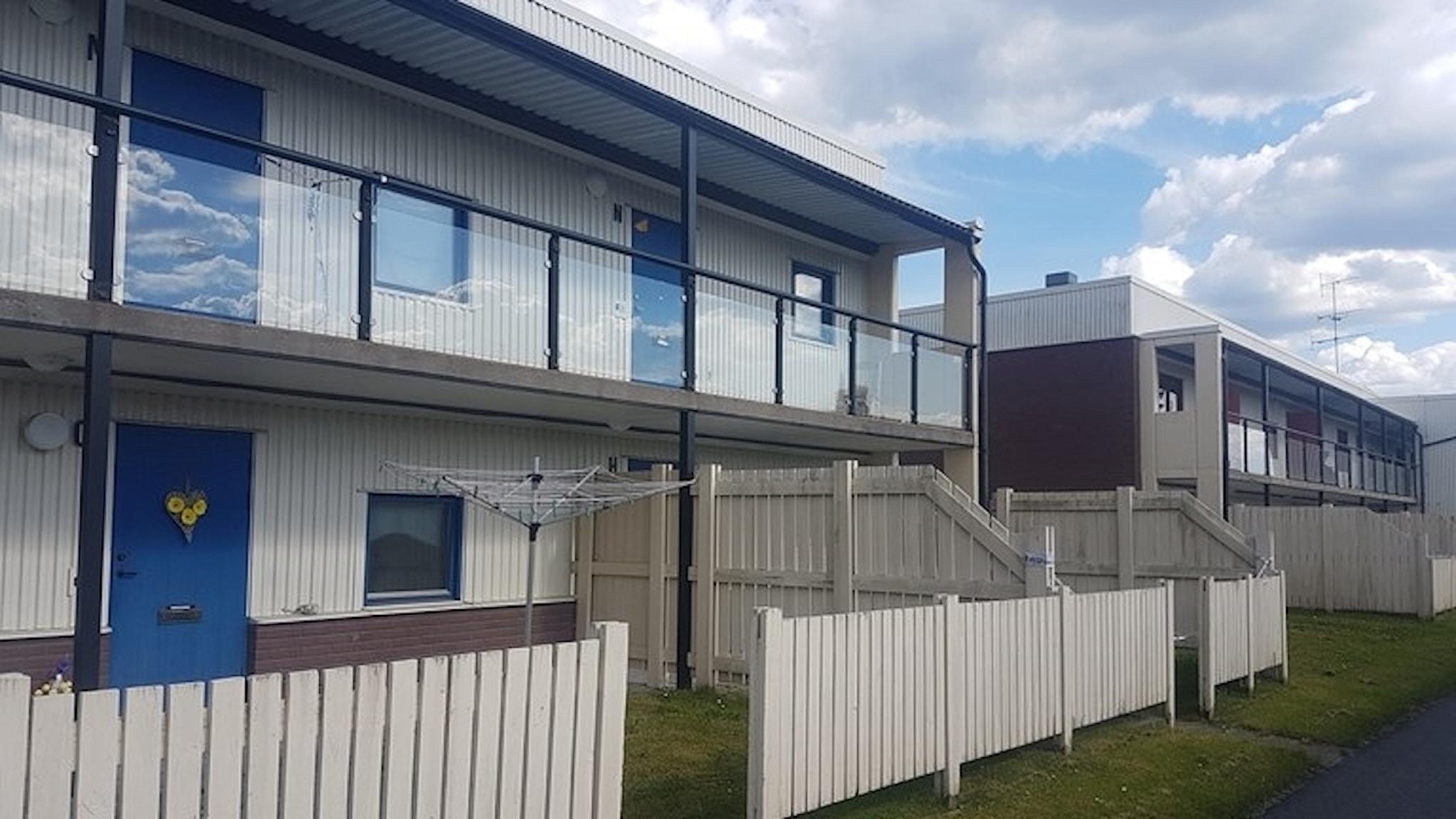 På fotet ser man ett vitt hus med blå dörrar. Det är två våningar högt och man kommer in till de övre lägenheterna via en loftgång.
