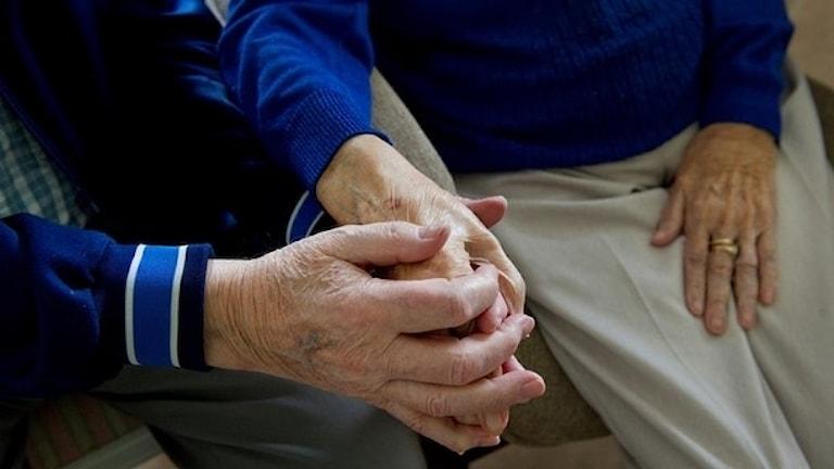 Ett äldre par håller varandra i handen.