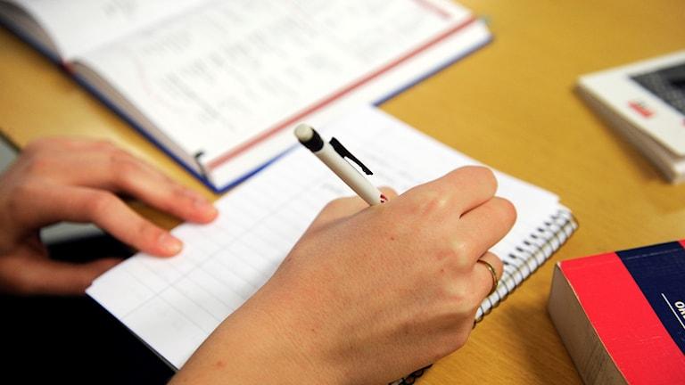 En kvinnlig hand skriver i ett anteckningsblock. Bredvid på bordet ligger böcker.