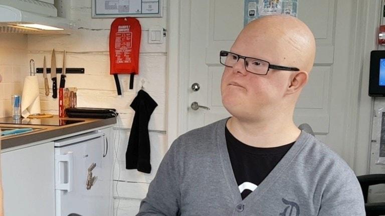 Fotot visar en flintskallig kille med svarta glasögon som sitter i ett kök.
