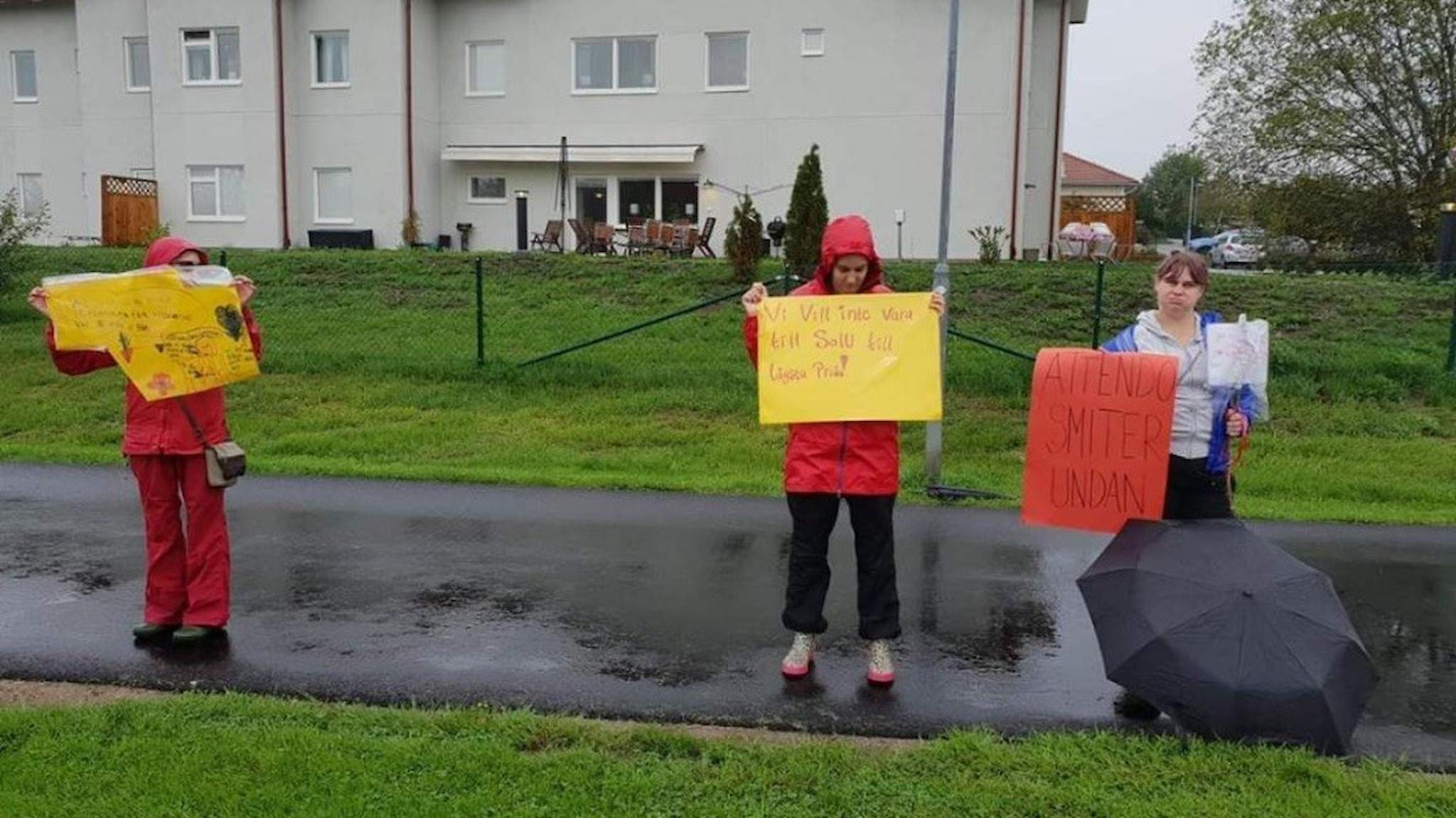 På fotot syns tre personer som håller upp plakat med texter.