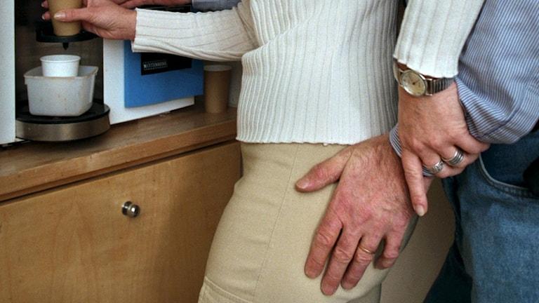 Fotot visar en kvinna hämtar kaffe vid en kaffeautomat och en man bakom henne håller handen på hennes lår.