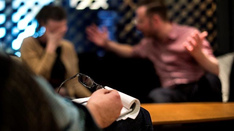 Fotot är suddigt. Man ser en man som pratar och gör stora gester med händerna. Kvinnan håller för munnen som om hon vore chockad.