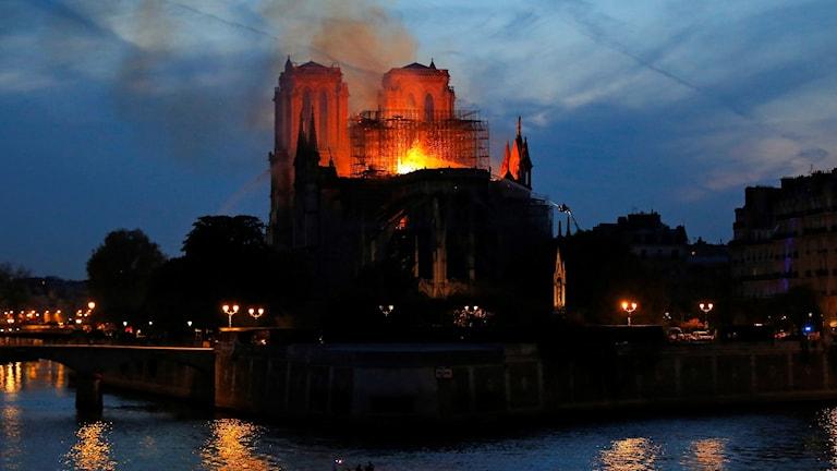 På fotot syns kyrkan i kvällens halvmörker. Röda eldslågor sticker upp genom taket. Elden speglas i flodens vatten.