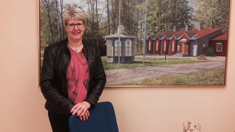 Hon står bredvid en tavla som föreställer äldre hus i Borlänge.