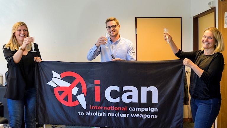 På fotot skrattar och skålar de med varandra. De håller upp en banderoll som har organisationens symbol.