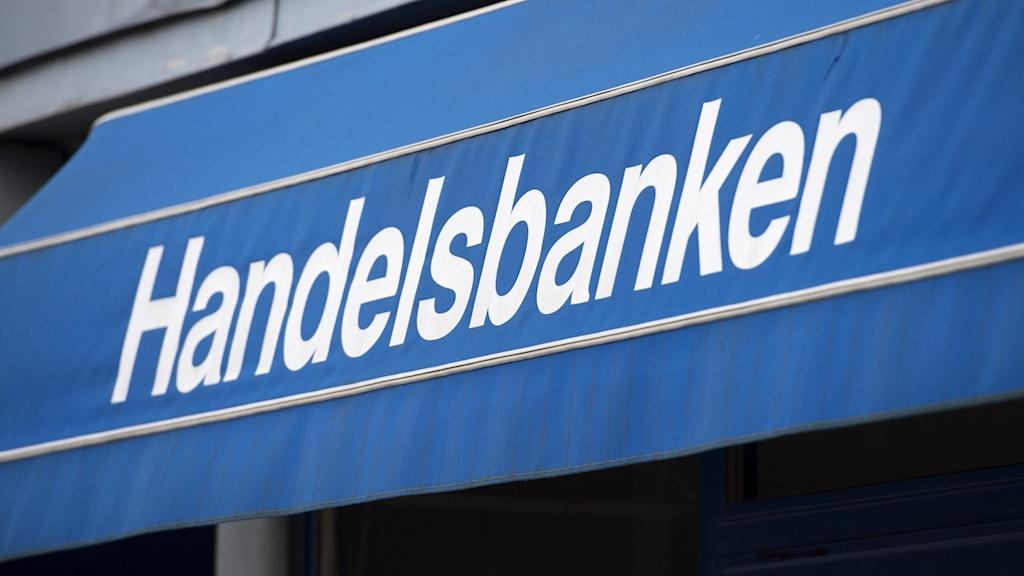 """På bilden ser man en blå markis där det står """"Handelsbanken"""" med vita bokstäver."""