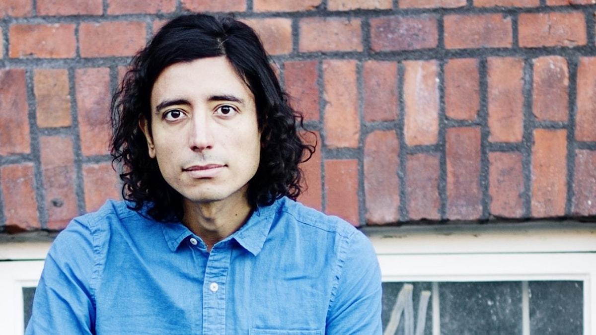 Författaren Inti Chavez Perez har mörkt hår, blå skjorta och jeans. Han sitter på en bänk utomhus framför en tegelvägg.