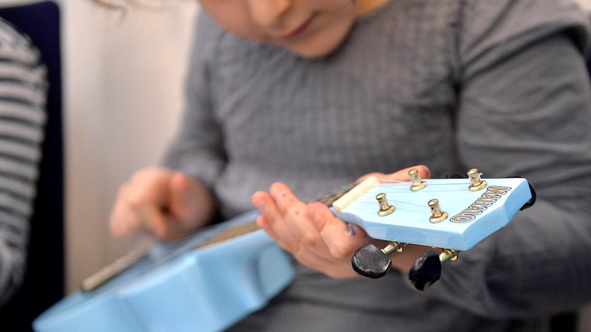 På fotot ser man ett barn som spelar på en litet blått instrument.Det ser ut att vara en liten gitarr eller en ukulele.
